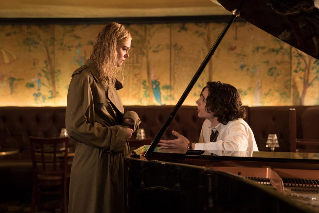 Ashleigh, gespielt von Elle Fanning, steht in A Rainy Day in New York durchnässt im Trenchcoat vor Gatsby, gespielt von Timothée Chalamet, der am Piano einer Hotelbar sitzt.