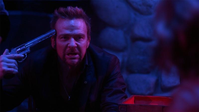 Kane sitzt am Tisch in einem schlecht beleuchteten Hinterzimmer und hält sich eine Waffe an die Schlefe in Acceleration - Gegen die Zeit