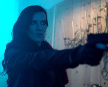 Rhona droht mit der Waffe, ihrem Blick nach ist sie zu allem bereit