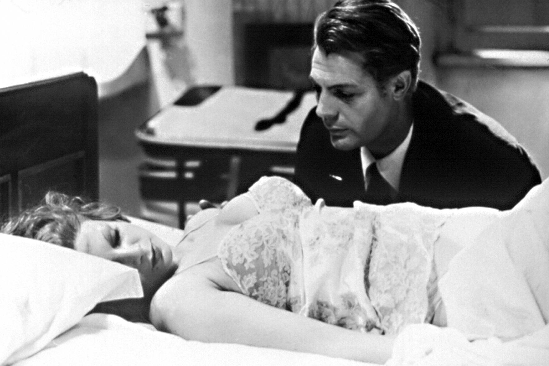 Guido Anselmi (Marcello Mastroianni) sitzt neben einem Bett und betrachtet die darin liegende, schlafende Blondine.