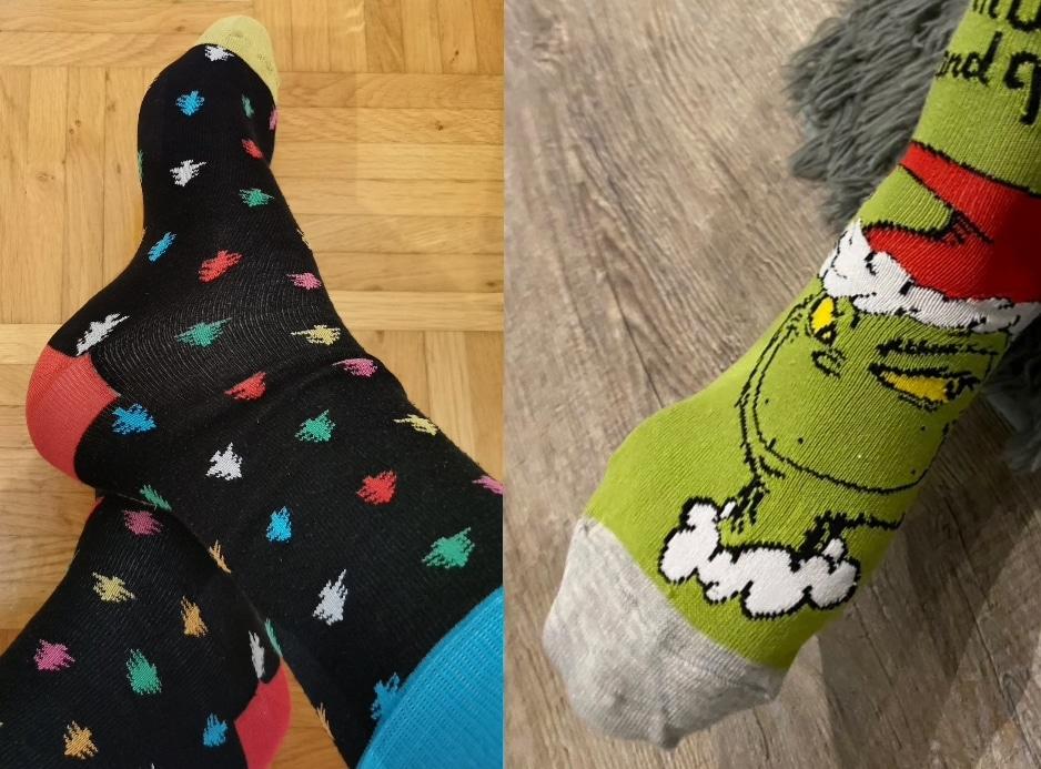 """Unsere beiden Sprecher tragen während der Aufnahme weihnachtliche Socken. Links ist ein schwarzes Paar mit knallbunten Weihnachtsbäumen in verschiedenen Farben. Rechts ein grüner Socken mit grauer Fußspitze. Als Motiv ist der Grinch mit Weihnachtsmütze zu sehen und darüber ein wenig der Text """"Naughty and Nice""""."""