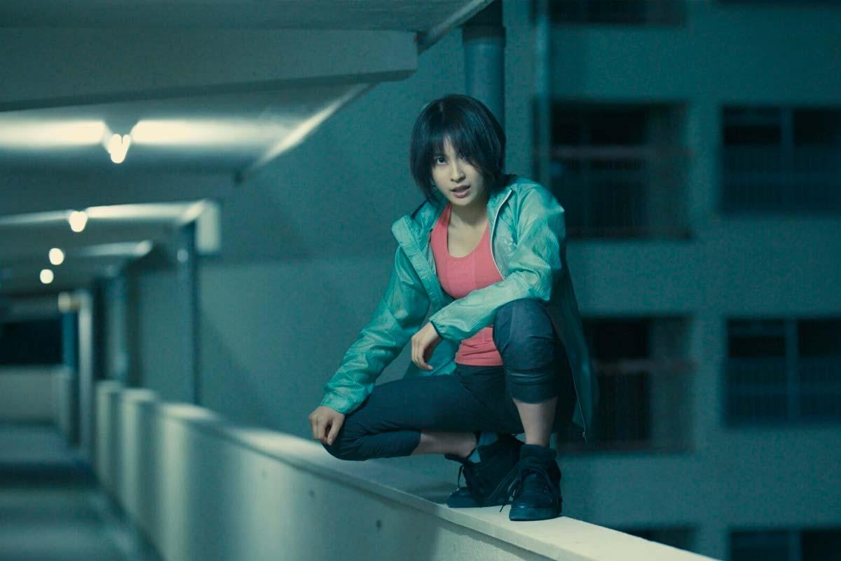 Usagi (Tao Tsuchiya) kniet auf dem Balkongeländer. Sie trägt schwarze Schuhe, eine dunkle Hose, ein rotes Top und darüber eine grüne Jacke.