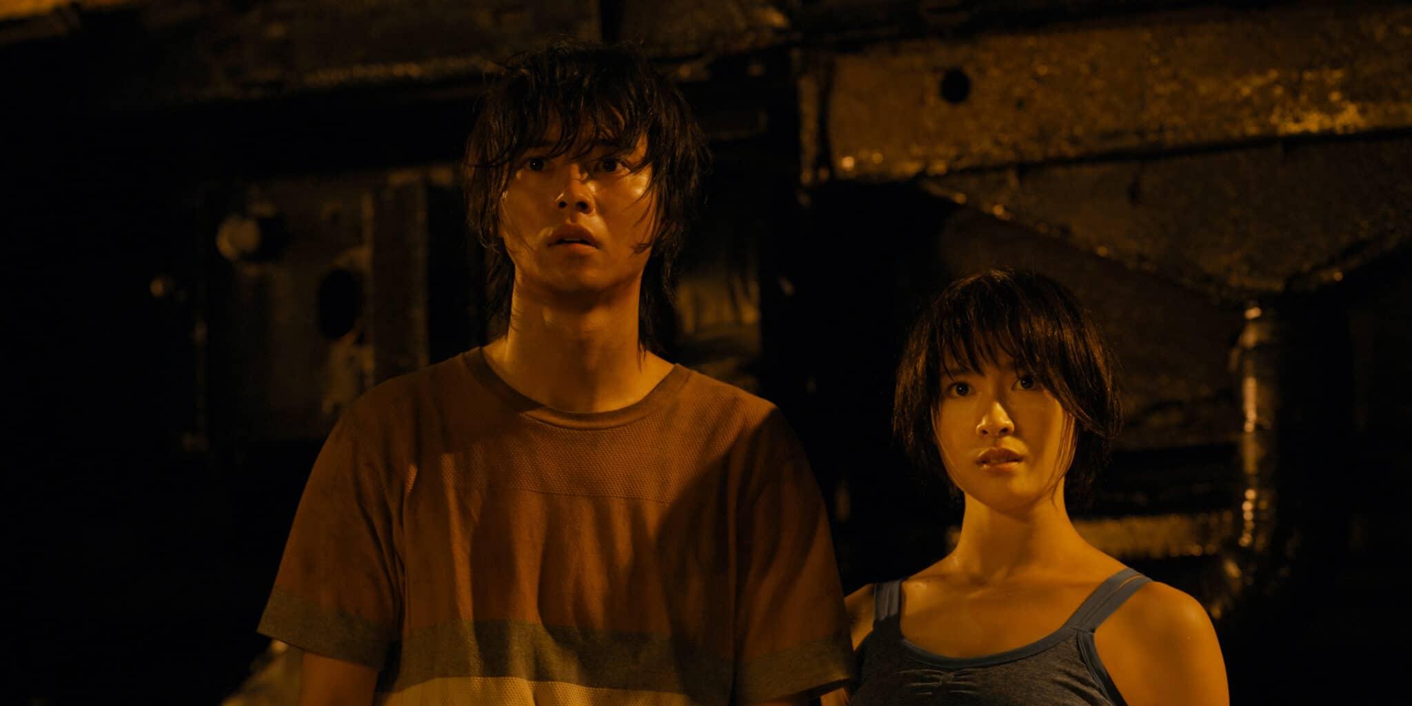 Arisu (Kento Yamazaki) und Usagi (Tao Tsuchiya) stehen in einem dunklen Raum. Er schaut erschrocken aus, sie hingegen wirkt entschlossen.