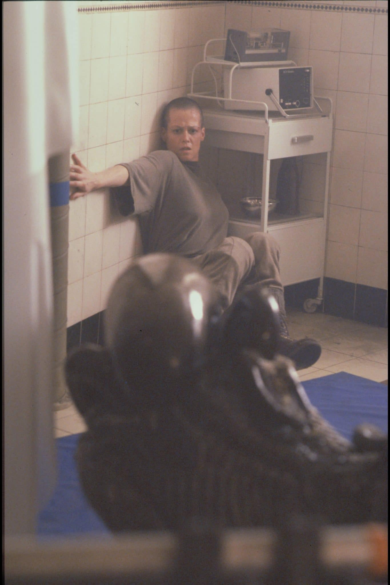 Ellen Ripley (Sigourney Weaver) blickt entsetzt in Richtung des Aliens, das man nur von hinten sieht. Sie sitzt vor medizinischen Geräten und vor einer weißgefliesten Wand auf dem Boden.
