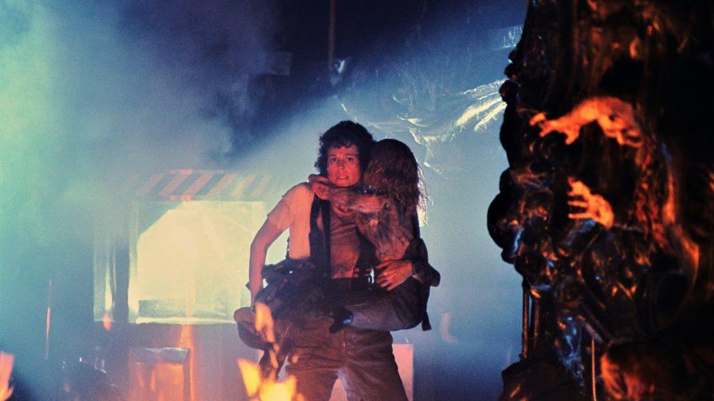 Ripley (Sigourney Weaver) versucht mit Newt auf dem Arm und bewaffnet mit einem Flammenwerfer in Aliens - Die Rückkehr einen Ausweg zu finden.