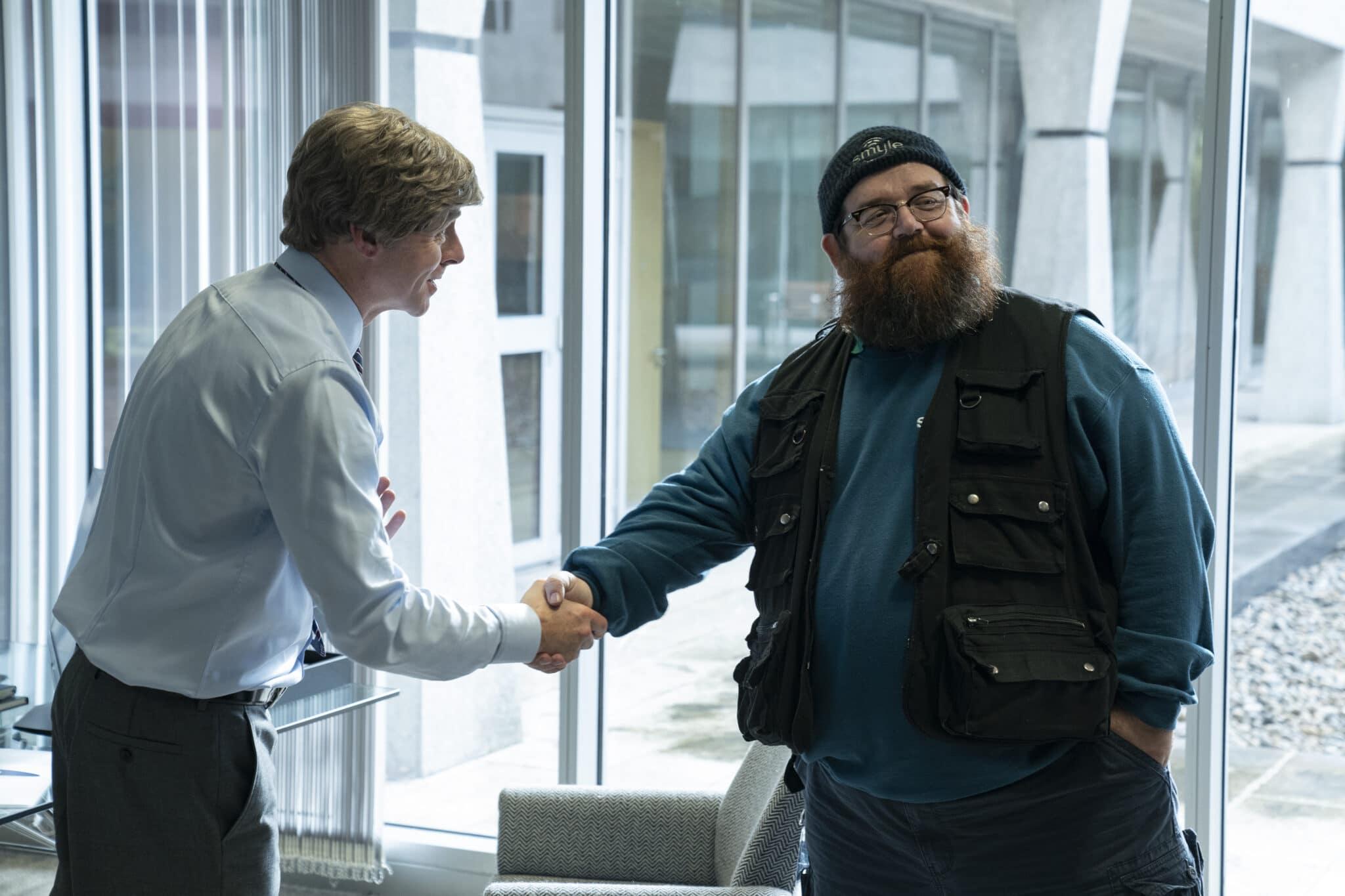 Dave (Simon Pegg) und Gus (Nick Frost) treffen sich in einem Büro mit Glasfassade und begrüßen sich mit einem Handschlag.