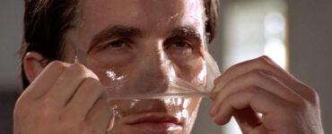 Christian Bale zieht sich als Patrick Bateman eine Schönheitsmaske vom Gesicht.