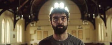 Alec Secareanu als Tomaz steht in Amulet - Es wird dich finden in einer Kirche.