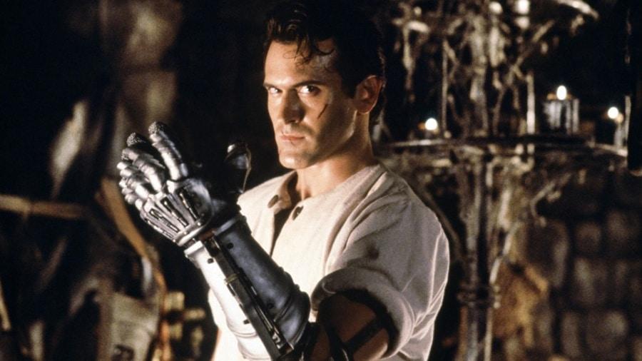 """Bruce Campbell blickt als Ash Williams in """"Armee der Finsternis"""" grimmig in die Kamera und präsentiert seinen metallenen linken Arm. Filme der 90er"""