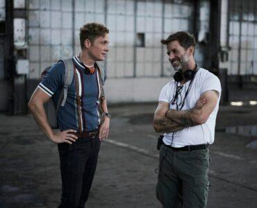 Der deutsche Schauspieler Matthias Schweighöfer trägt eine dunkle Jeans, ein blaues T-Shirt mit Lederhosenträger und einen grauen Rucksack. Er stemmt die Hände in die Hüfte und unterhält sich mit dem US-Regisseur Zack Snyder, der ein weißes T-Shirt, olivfarbene Hosen und Kopfhörer um den Hals trägt und die lächelnd die Arme verschränkt. beide stehen in einer alten Lagerhalle bei Dreharbeiten zu Army Of The Dead, auf dem Steinboden sind Wasserpfützen zu sehen. © Netflix