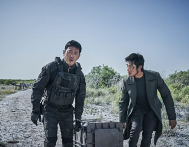 Die beiden Hauptfiguren Jo und Lee versuchen gemeinsam einen Behälter mit den Sprengköpfen zum Berg zu tragen. Beide sind gezeichnet von ihrem Verletzungen. Lee strömt das Blut von seinem Kopf links das Gesicht runter.