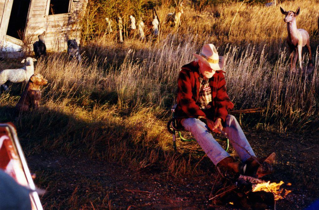 Auf einem der vielen Halte in The Straight Story sitzt Alvin Straight am eigenen Lagerfeuer und ist eins mit sich und der Natur in The Straight Story von 1999.