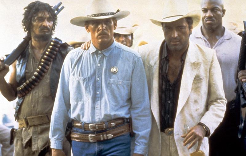 Powers Boothe packt Nick Nolte an der Schulter, während hinter ihm seine Bodyguards auf ihn achten in Ausgelöscht