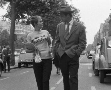 Michel Poiccard (Jean-Paul Belmondo) und Patricia (Jean Seberg) schlendern in Außer Atem die Champs-Élysées entlang. Sie gucken sich dabei gegenseitig an.
