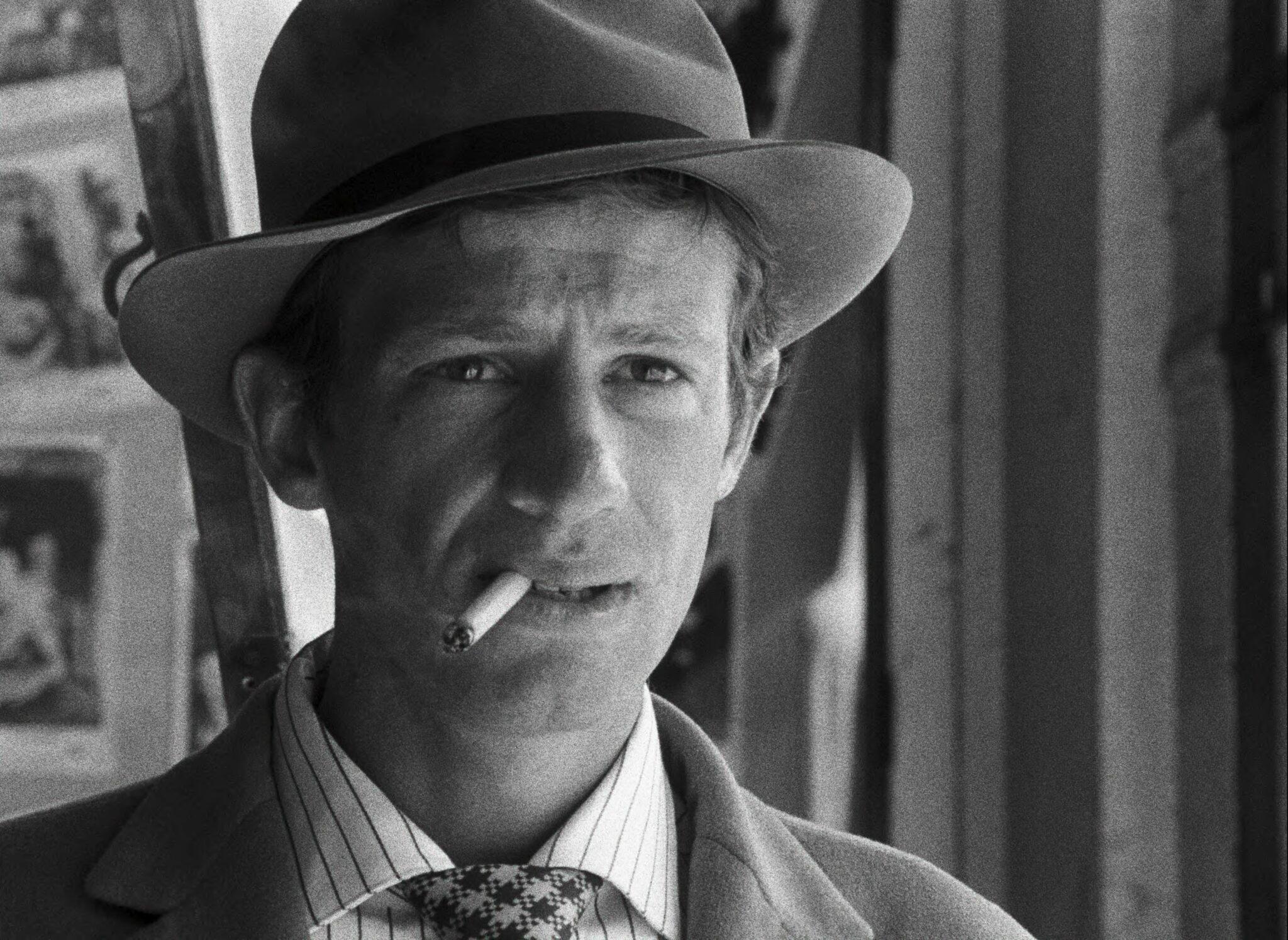 Michel (Jean-Paul Belmondo) in Außer Atem mit angestrengtem Blick. Er trägt einen Hut und lässt die Zigarette lässig im Mundwinkel liegen.