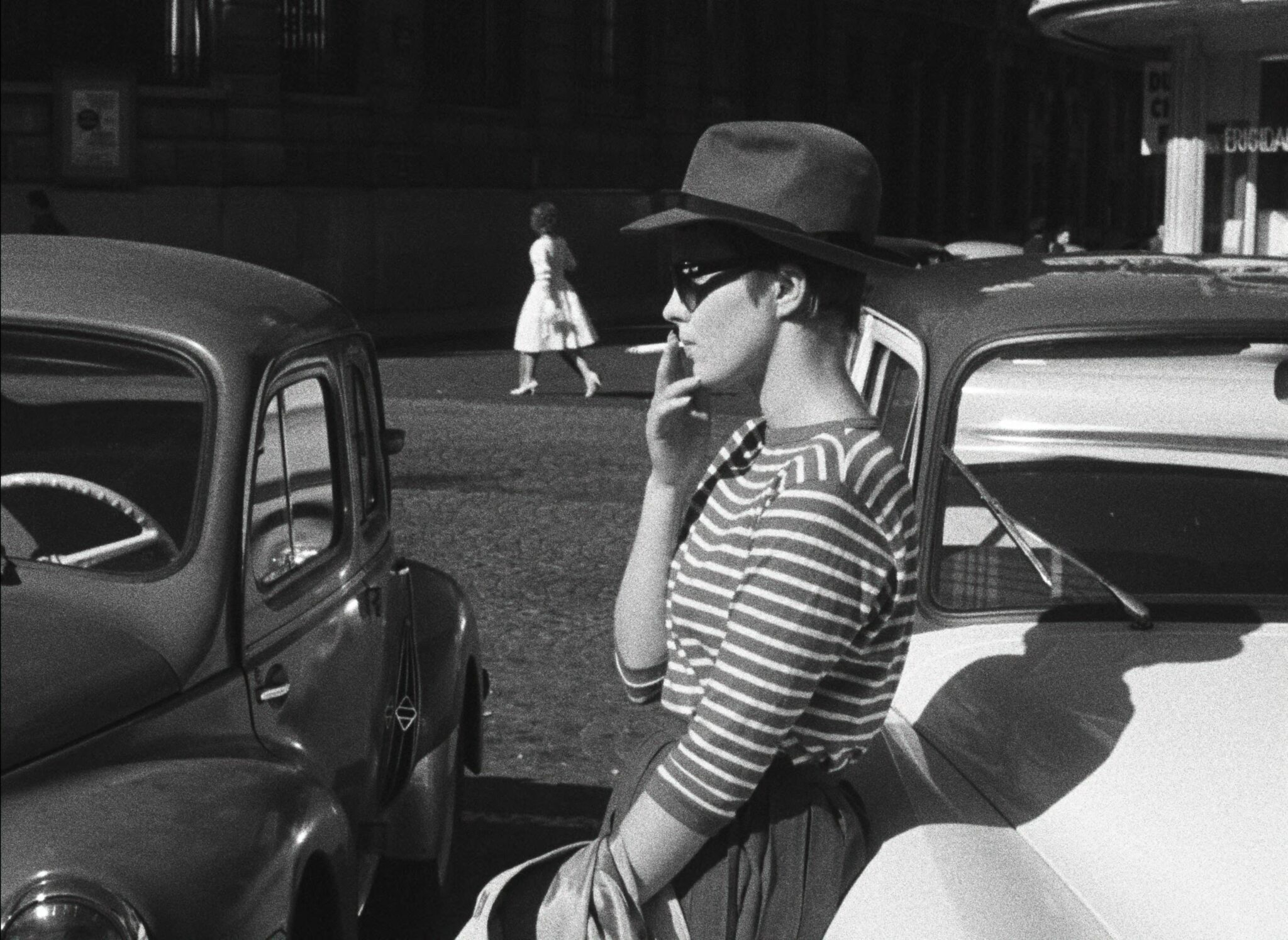 Patricia (Jean Seberg) lehnt in Außer Atem entspannt an einem Auto. Mit der rechten Hand führt sie sich die Zigarette zum Mund. Dabei trägt sie Michels (Jean-Paul Belmondo) Hut und eine Sonnenbrille.