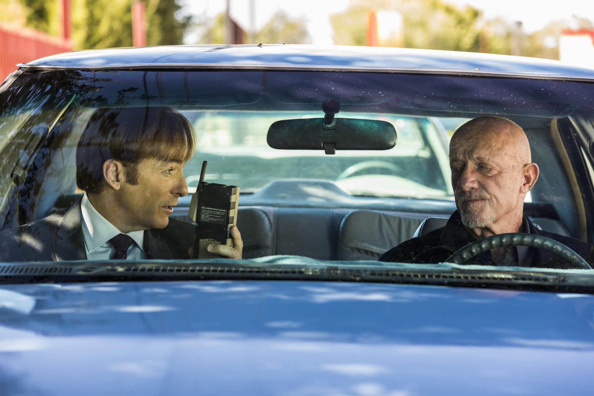 Jimmy (Bob Odenkirk) und Mike (Jonathan Banks) fahren in einem blauen Wagen. Sie blicken sich gegenseitig an während Jimmy ein Telefon hochhält.