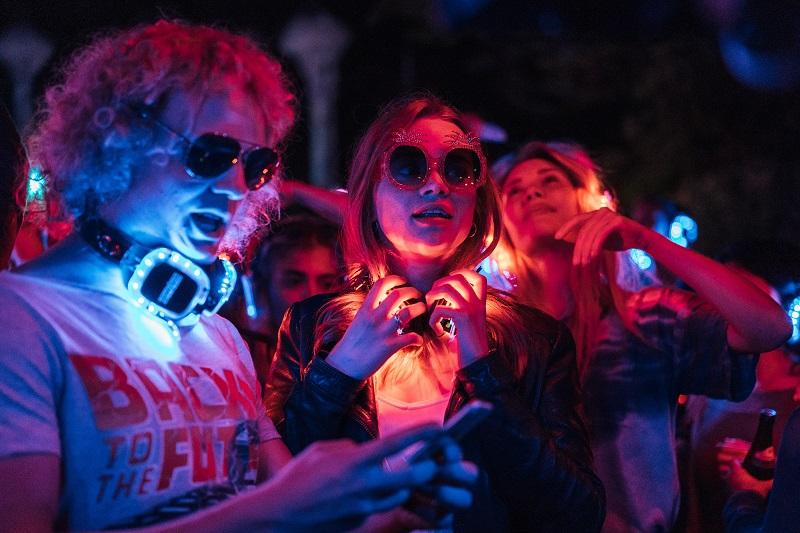 Im bunten Licht des Techno-Clubs tauschen drei Partygänger Nummer aus - Neu auf Netflix im August 2020