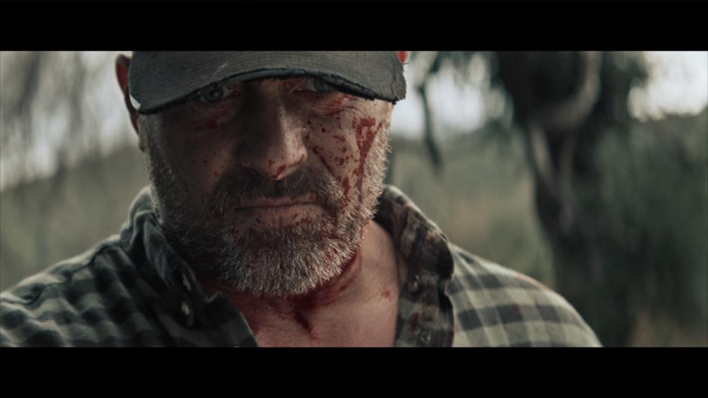 Frank Wilson (Johnny Messner) mit blutverschmierten Gesicht. Er jagt die Mörder seines Sohnes.