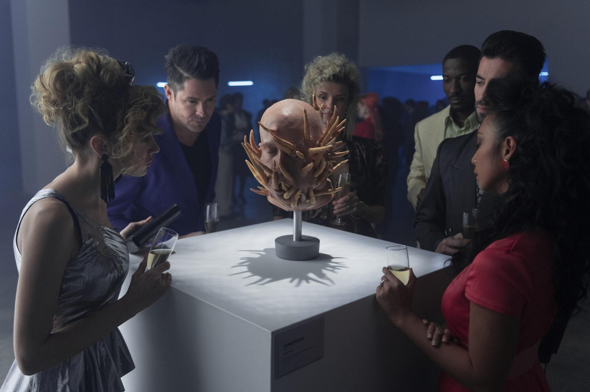 Sechs Personen stehen um ein Podest herum, auf dem eine Skulptur steht, die einen Schädel mit Stacheln übersät zeigt.