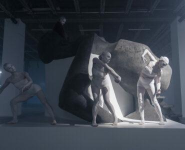 Auf einer Vernissage: Drei Personen bei einer Performance Kunstinstallation
