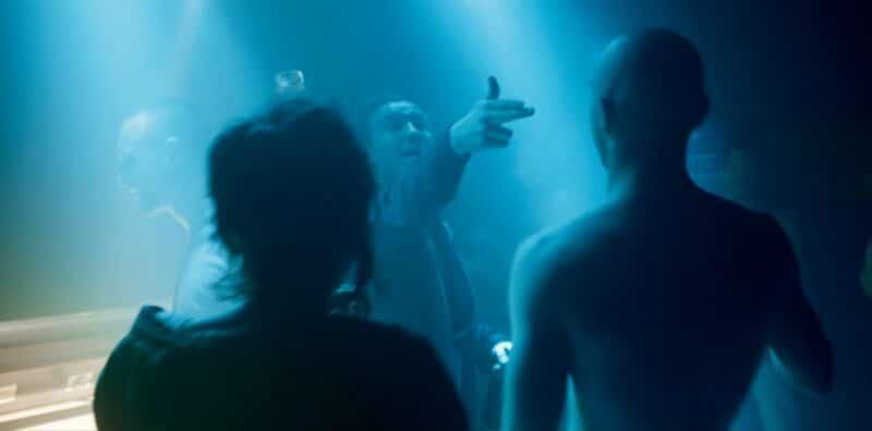 Sonne formt mit seinen Fingern eine Pistole und richtet sie auf Boxer, sie stehen in blauem Licht