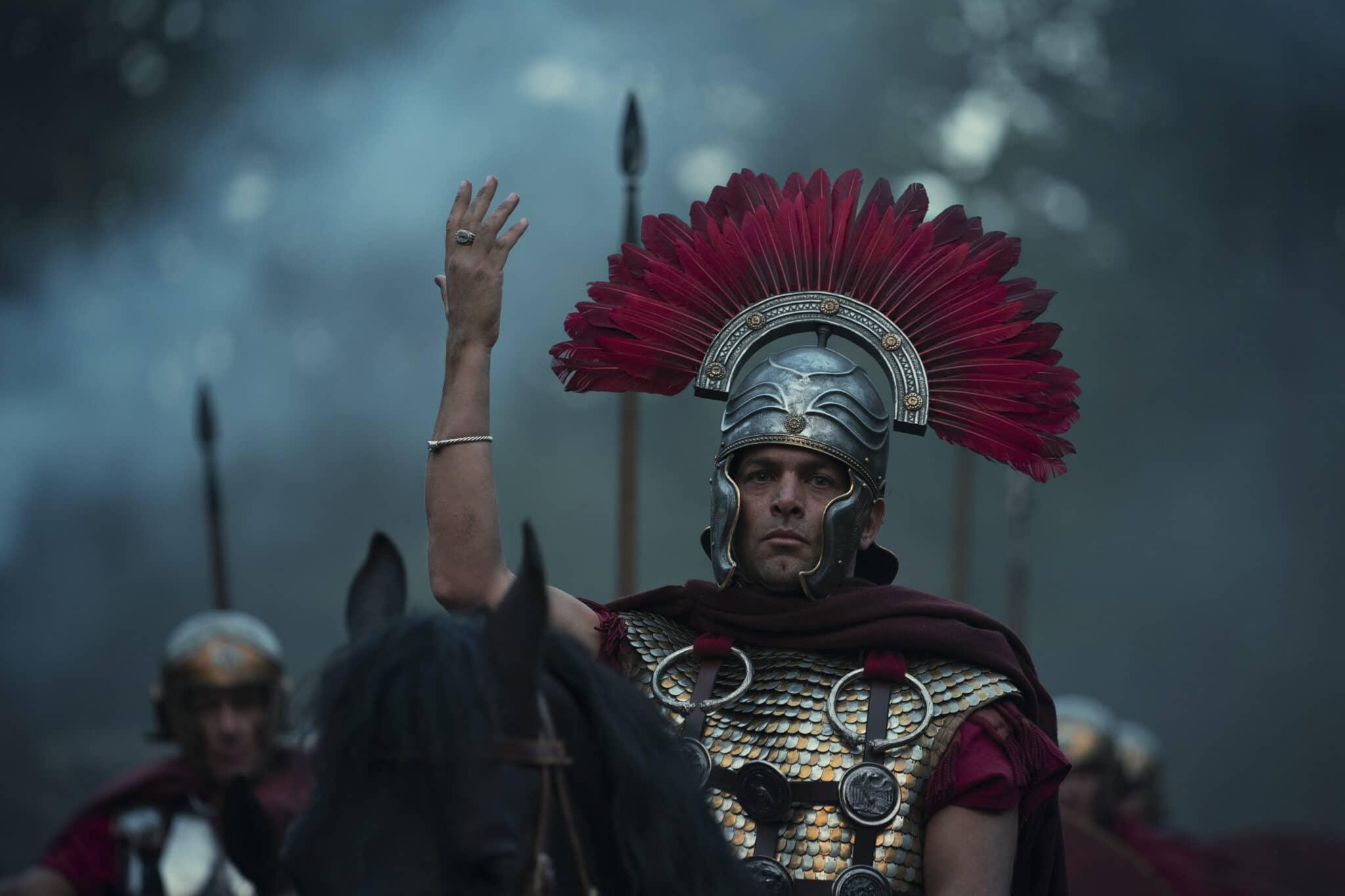 Ein römischer Legionär mit Federhelm sitzt mit erhobener Hand auf einem schwarzen Pferd. Im Hintergrund sieht man verschwommen weitere Legionäre.