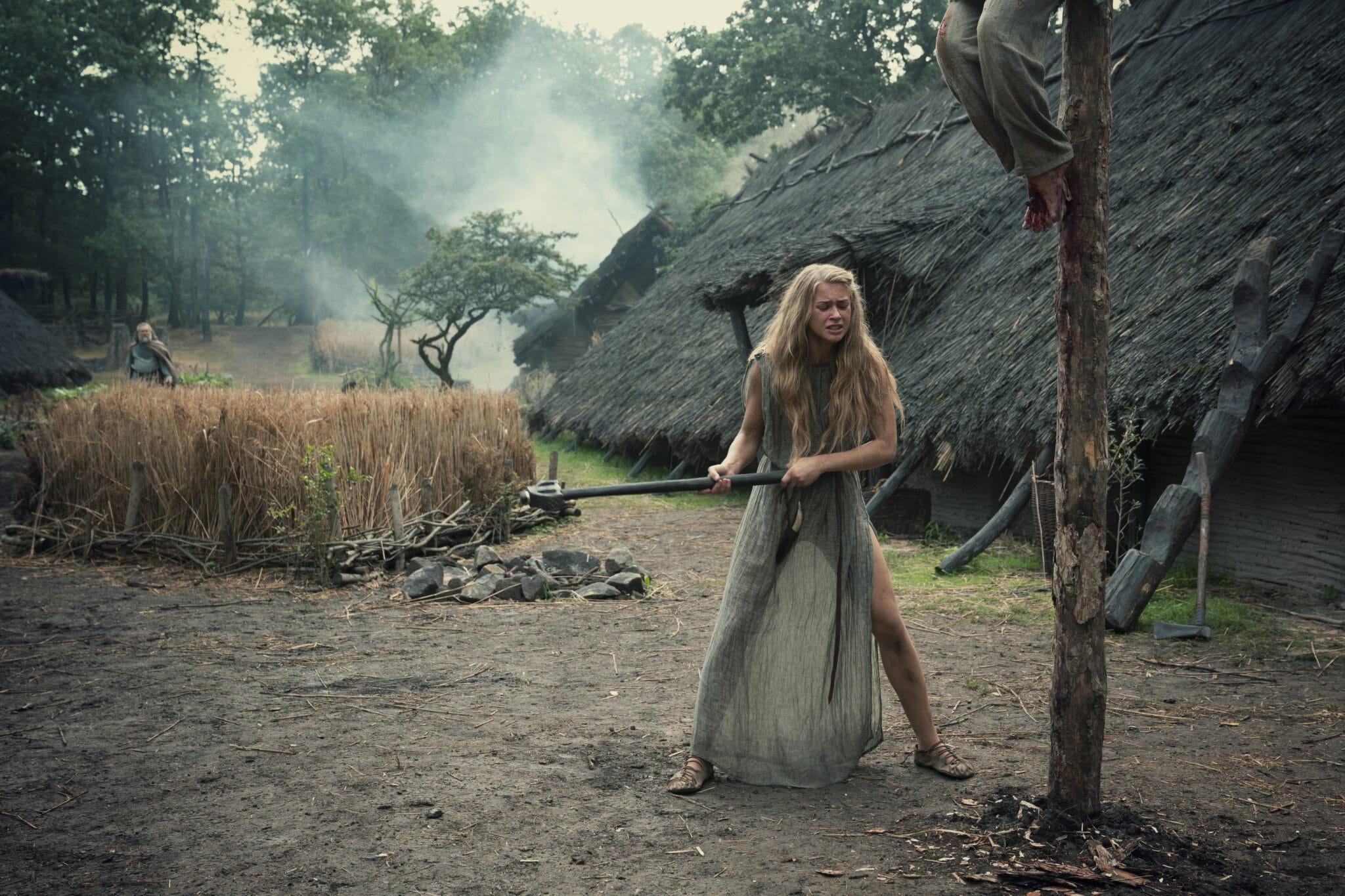 Thusnelda (Jeanne Goursaud) hält eine Art Axt in den Händen und schwingt Richtung eines Pfahls, um diesen zu Fall zu bringen. Im Hintergrund steht ein Reetdachhaus.