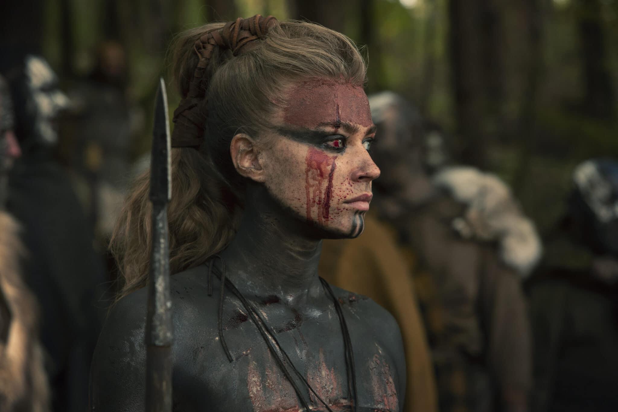 Thusnelda (Jeanne Goursaud) ist komplett mit Blut und schwarzer Farbe überzogen. Sie blickt mit ernster Miene für den Betrachter nach rechts. Ihr rechtes Auge ist dabei blutunterlaufen.