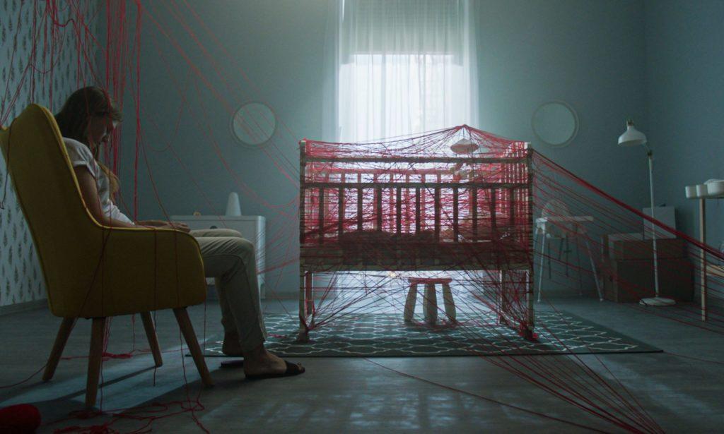 In Baba Yaga hinterlässt die böse Hexe in Form von roten Fäden ihre Spuren. Hier sieht man ein Kinderbett, dass von diesen umgarnt ist, während die Mutter fassungslos in die Leere starrt.