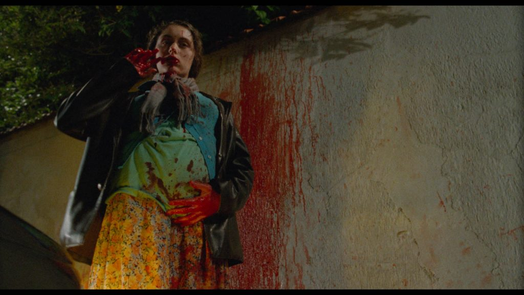 Die Mutter steht blutverschmiert vor einer Wand und hält sich ihren runten Babybauch