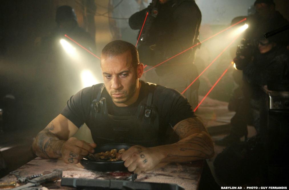"""Vin Diesel als Toorop sitzt in """"Babylon A.D."""" an einem Tisch, während mehrere Soldaten ihre Waffen auf ihn gerichtet haben und ihn dabei mit ihren Laseraufsätzen rot anleuchten."""