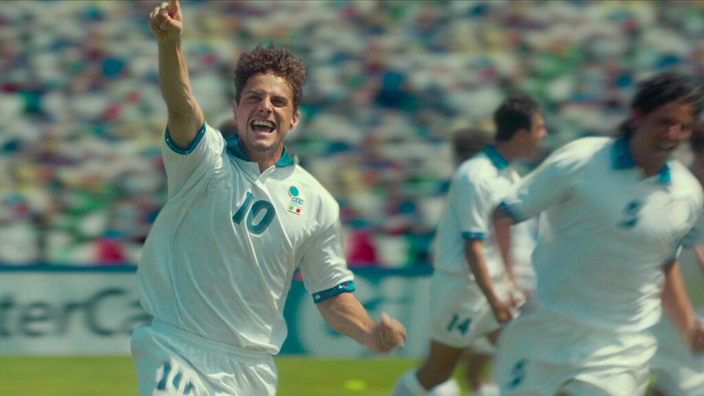 Roberto Baggio - das göttliche Zöpfchen (Andrea Arcangeli) bejubelt ein von ihm erzieltes Tor und reckt seinen Finger in die Höhe. Dabei trägt er das Trikot der italienischen Nationalmannschaft mit der Nummer 10. © Netflix