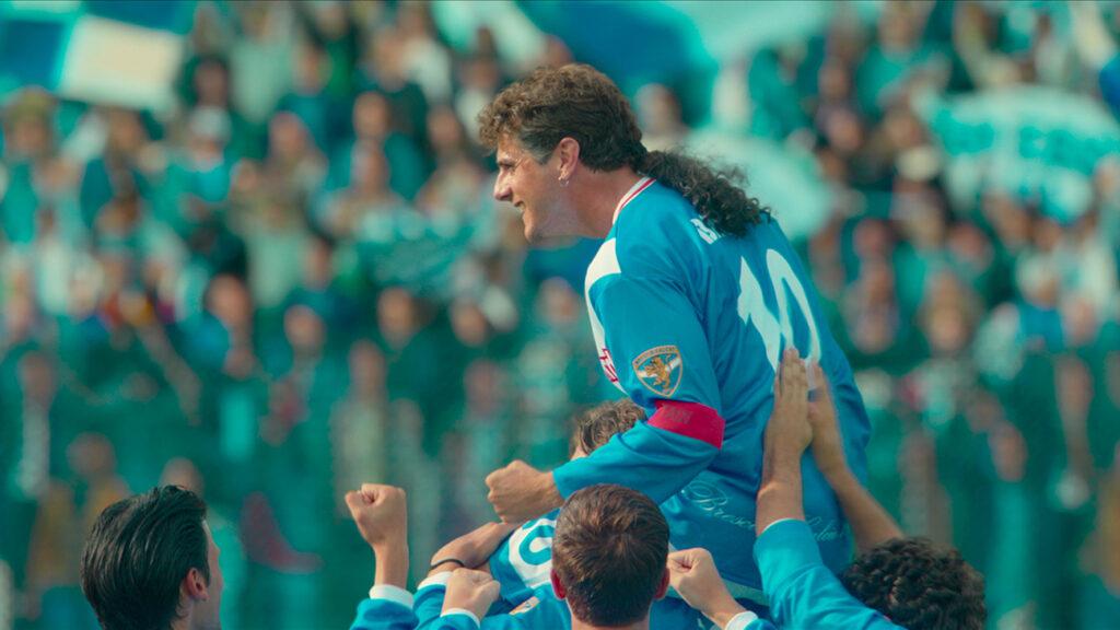 Roberto Baggio (Andera Arcangeli) wird zum Ende seiner Karriere bei Brescia Calcio von seinen Mitspielern gefeiert. Diese heben ihn zusammen in die Luft empor, nachdem er ein wichtiges Tor erzielt hat. Baggio - Das göttliche Zöpfchen ® Netflix