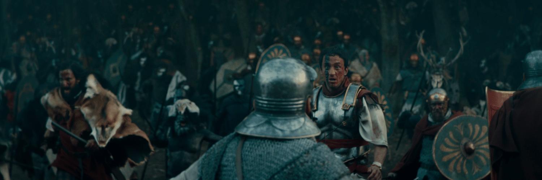 Arminius schaut mitten im Schlachtgetümmel von Barbaren überrascht und angestrengt, mit rot-schwarzer Kriegsbemalung im Gesicht. Um ihn herum bekämpfen sich etliche Krieger.