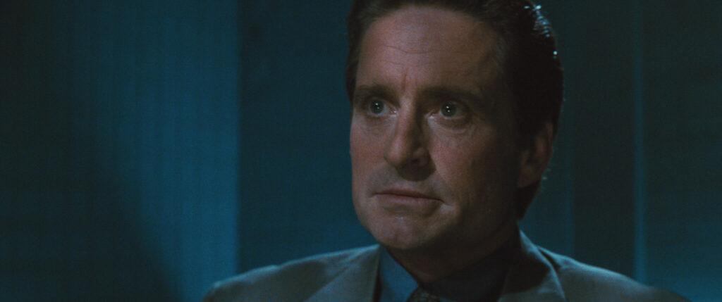"""Michael Douglas spielt in """"Basic Instinct"""" Detective Nick Curran, der hier auf dem Bild etwas schockiert, aber doch ernster Miene, auf etwas oder jemanden schaut."""