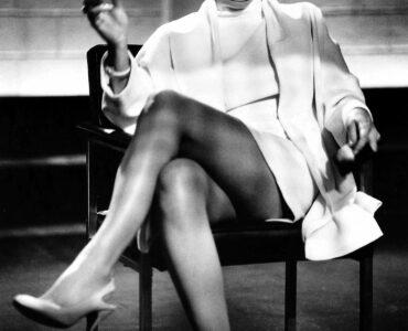 """Auf dem Bild ist Sharon Stone in der berühmten Verhörszene aus """"Basic Instinct"""" zu sehen. Das Bild hier ist in schwarz-weiß gehalten. Stone sitze auf einem Stuhl, hinter ihr ist eine kahle Mauerwand. Sie hat das linke Bein über das rechte geschlagen und hält in ihrer rechten Hand eine Zigarette. Ihr Blick ist selbstbewusst auf jemanden oder etwas außerhalb des Bildes gerichtet."""