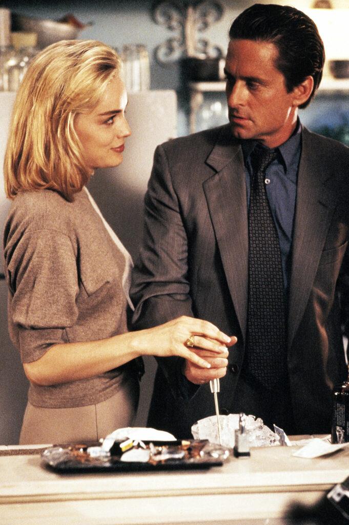Det. Nick Curran (Michael Douglas) hält in seiner rechten Hand einen Eispickel, welcher noch in einem Eisblick steckt. Die attraktive Catherine Tramell (Sharon Stone) legt ihre recht Hand auf die Hand des Detektivs und blickt diesen sehr verführerisch an. Nick erwidert den Blick, allerdings etwas erschrocken bzw. der Schönheit verfallend.