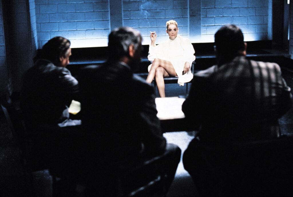 Catherine Tramell (Sharon Stone) wird verhört. Auf dem Bild sitzt sie weiter entfernt. Als Betrachter steht man hinter den Beamten, die sie verhören. - Basic Instinct