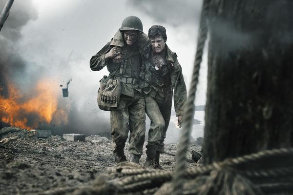 Im Hintergrund die Flammenhölle schleppen sich zwei Soldaten vom Schlachtfeld in Hacksaw Ridge - Die Entscheidung