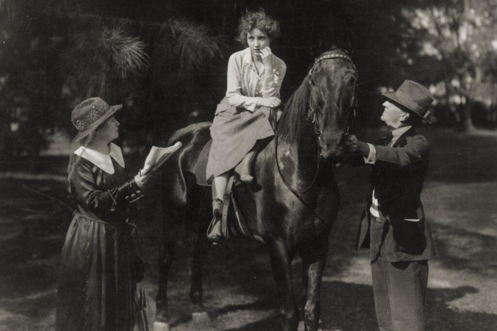 Darstellerin auf einem Pferd bespricht die nächste Szene mit Regisseurin Alice Guy-Blaché BE NATURAL: SEI DU SELBST