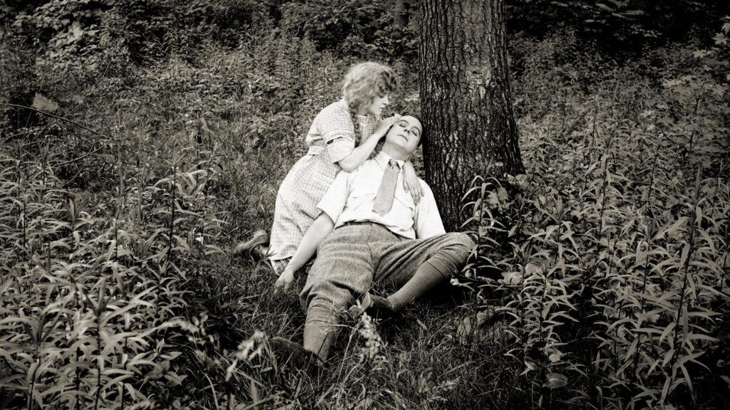 Mann liegt unter einem Baum in den Armen einer Frau, Screenshot eines Films von Alice Guy_Blaché
