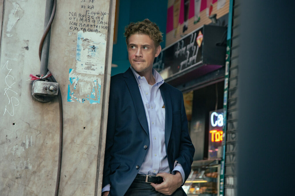 """Boyd Holbrook steht in einer Ladentür und beobachtet etwas oder jemanden. - """"Beckett"""""""