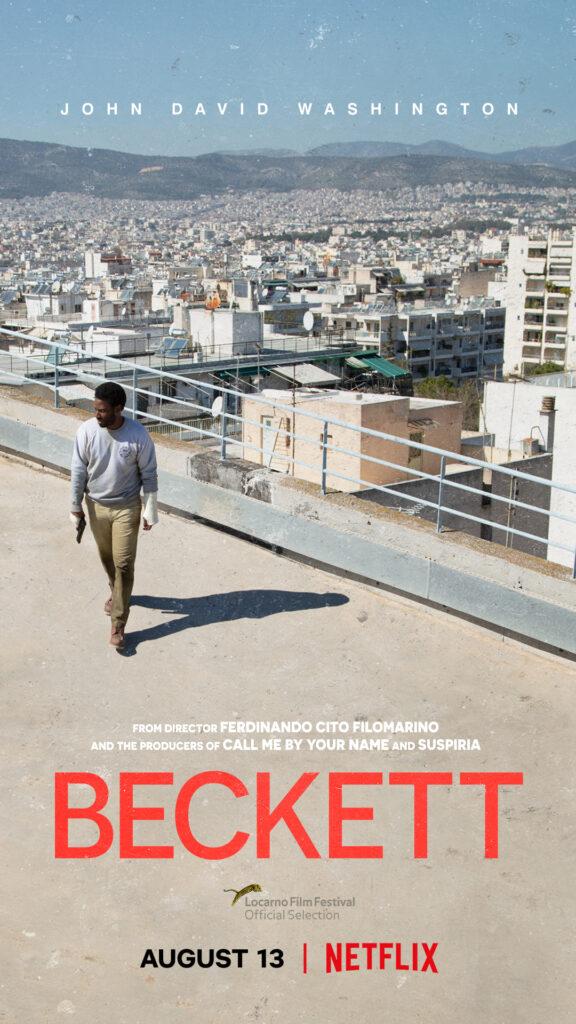 """Das internationale Filmplakat zu """"Beckett"""" zeigt Hauptfigur Beckett aus einer diagonalen Vogelperspektive. Dieser steht scheinbar auf einem Hochhaus mit Blick auf eine Stadt bzw. mehrere andere Gebäude. Er geht von der Brüstung weg und hält in seiner rechten Hand eine Waffe."""
