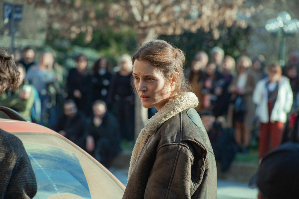 """Aktivistin Lena (Vicky Krieps) steht am Ende eines Autos vor dem Kofferraum und unterhält sich mit jemanden außerhalb des Bildes. - """"Beckett"""""""