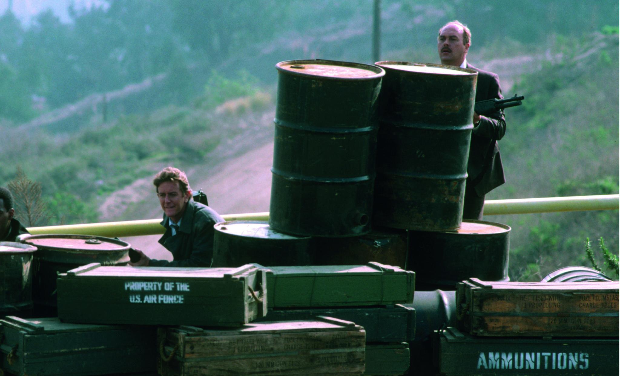 Billy Rosewood (Judge Reinhold) und John Taggart (John Ashton) suchen sich im Finale von Beverly Hills Cop II Deckung hinter Fässern und Kisten.