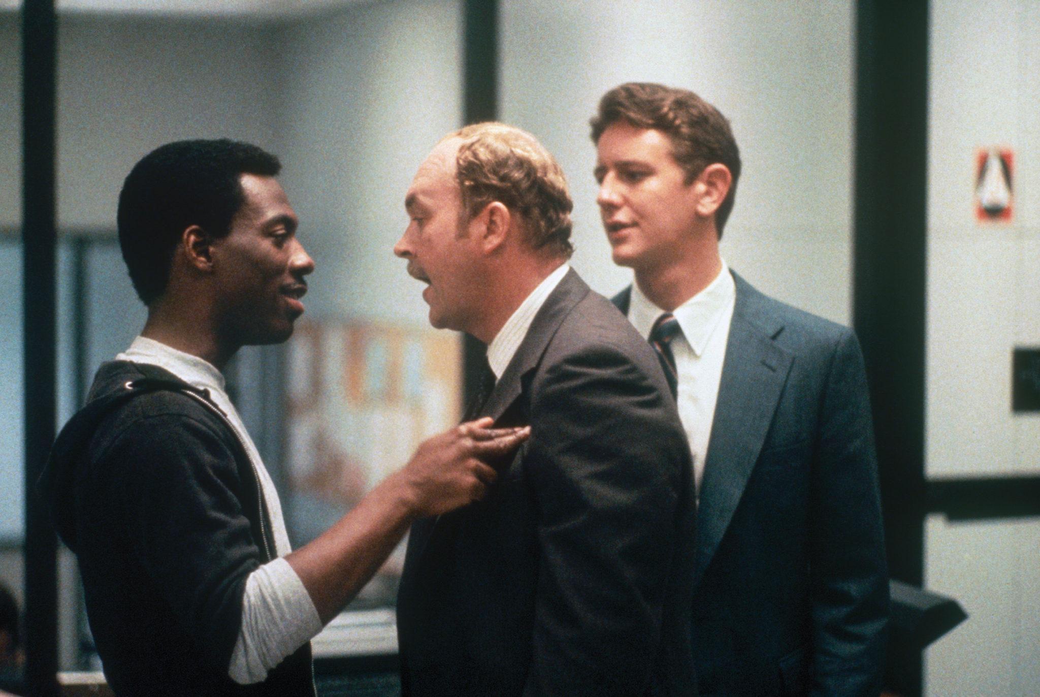 Axel Foley (Eddie Murphy) befindet sich im Streitgespräch mit Taggart (John Ashton) und Rosewood (Judge Reinhold) in Beverly Hills Cop.