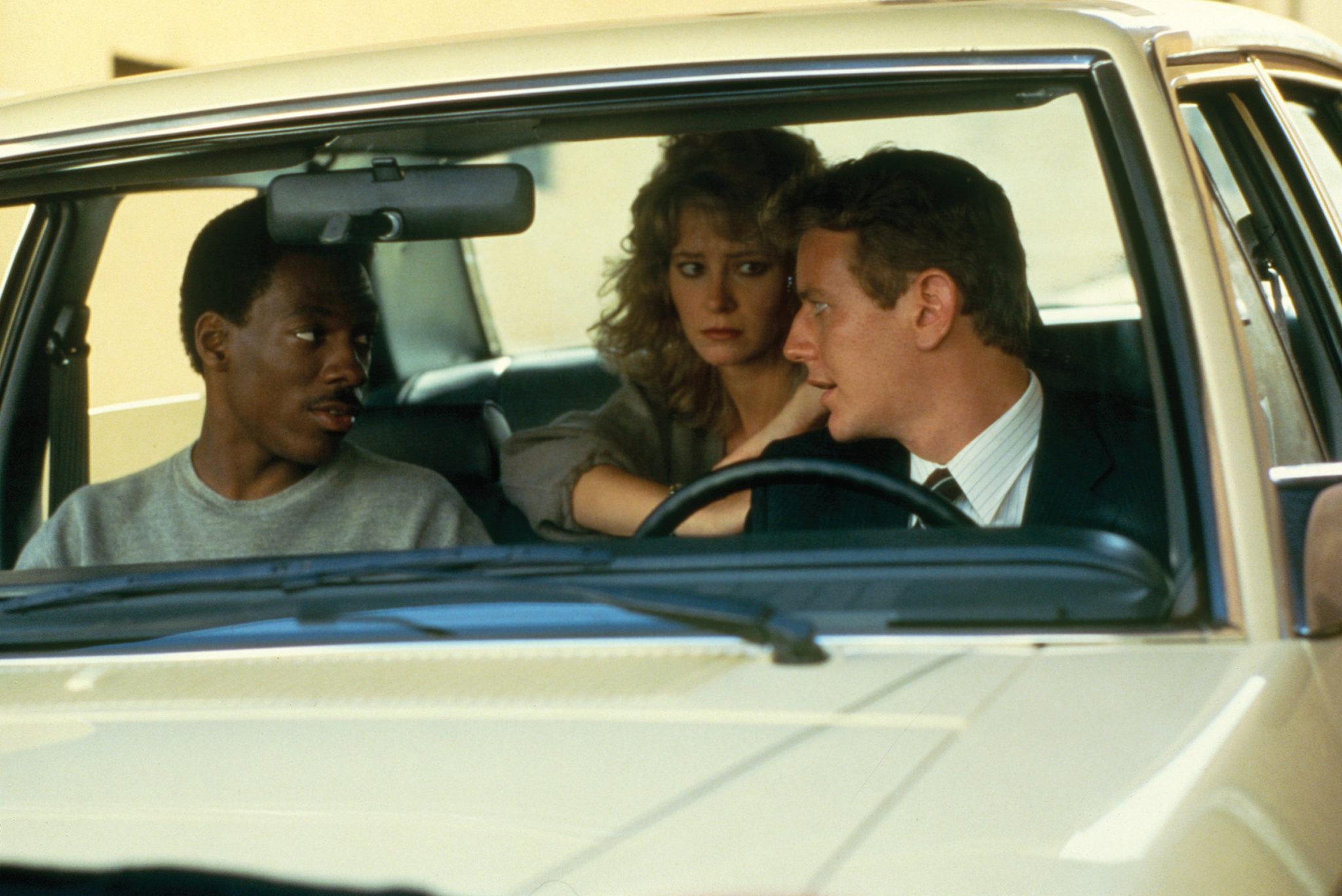In einem beigen Auto sitzen Axel Foley (Eddie Murphy) auf dem Beifahrersitz, Jenny Summers (Lisa Eilbacher) auf der Rückbank und Billy Rosewood (Judge Reinhold) auf dem Fahrersitz. Die Lage scheint angespannt.