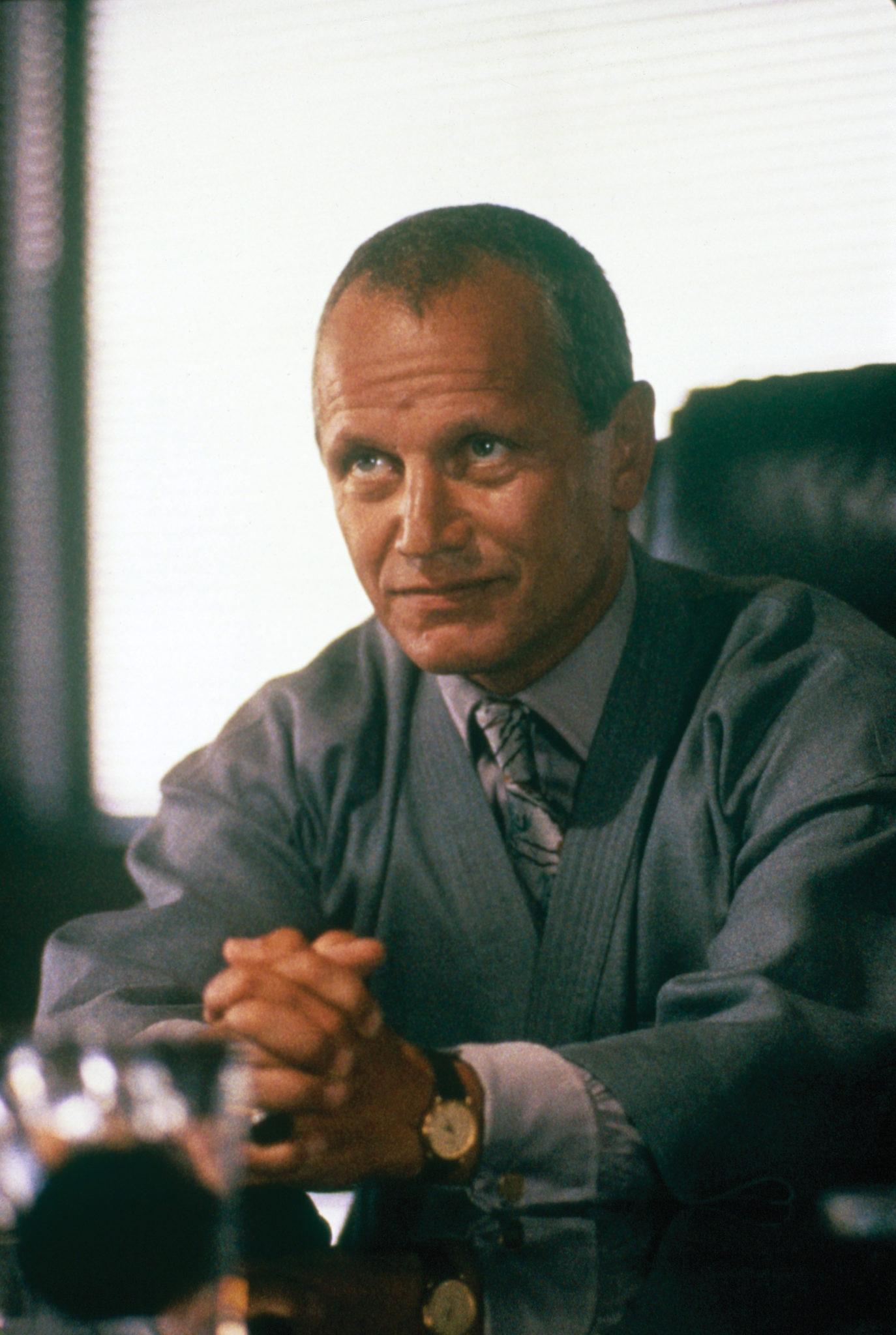 Victor Maitland (Steven Berkoff), der Antagonist aus Beverly Hills Cop, sitzt in seinem Büro, die Hände lehnen mit den Fingern ineinander verschränkt auf dem Tisch.