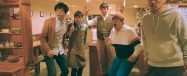 Kato blickt mit seiner Kellnerin und seinen drei Freunden, die sich alle um den TV versammelt haben, fasziniert gen Kamera - Beyond the Infinite Two Minutes